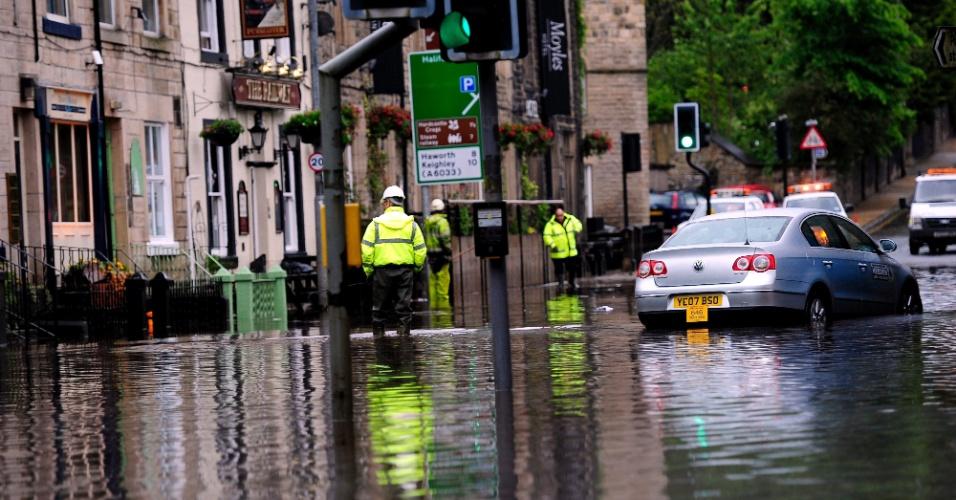 23.jun.2012 - Equipes de emergência inspecionam rua alagada em Hebden Bridge, no condado de West Yorkshire , no Reino Unido