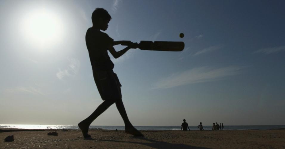 23.jun.2012 - Garoto joga críquete na praia Marina, na cidade indiana de Chennai