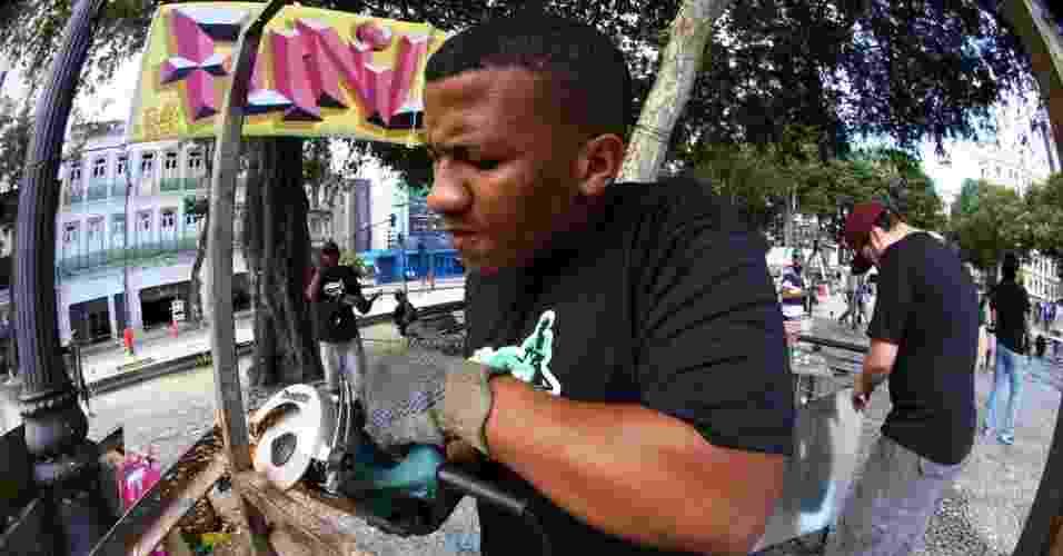 """Grafiteiro pinta carroça de catador de lixo, durante o """"Pimp my carroça"""", no Rio de Janeiro (23/6/12) - Ricardo Cassiano/UOL"""