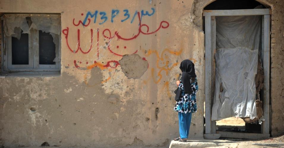24.jun.2012 - Garota aguarda na parte externa de uma casa em Garmser, no Afeganistão