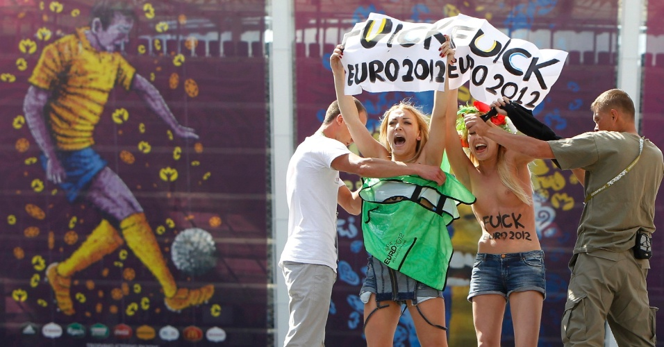 24.jun.2012 - Homens tentam cobrir manifestantes do grupo feminista Femen em protesto no estádio olímpico em Kiev, na Ucrânia, durante partida do campeonato Euro 2012. O grupo tem organizado vários protestos sob o lema