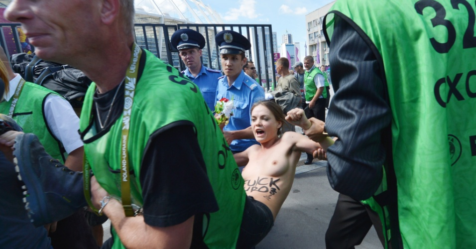 24.jun.2012 - Policiais detêm manifestante do grupo feminista Femen que protestava no estádio olímpico em Kiev, na Ucrânia, durante partida do campeonato Euro 2012. O grupo tem organizado vários protestos sob o lema