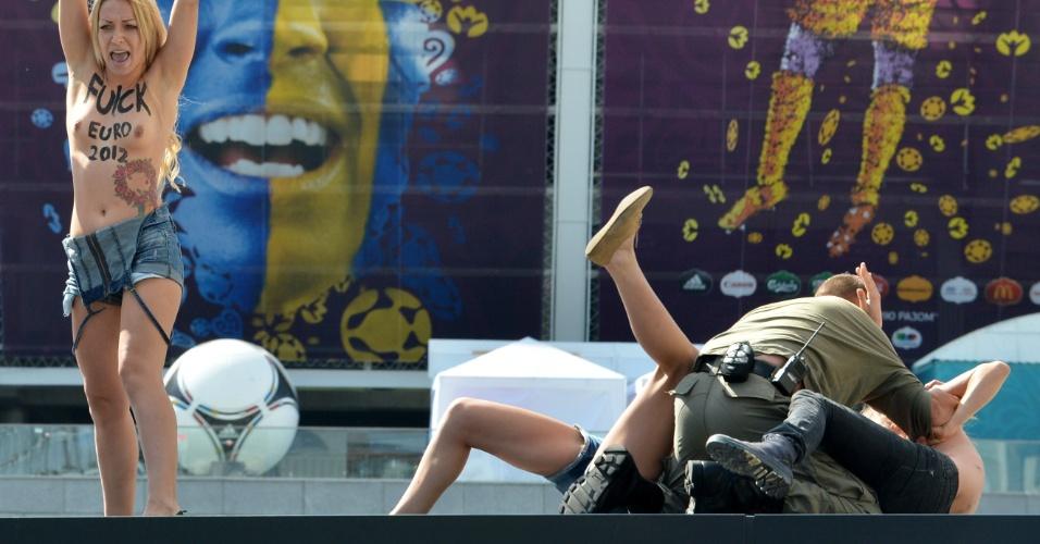 24.jun.2012 - Policiais detêm manifestantes do grupo feminista Femen em protesto no estádio olímpico em Kiev, na Ucrânia, durante partida do campeonato Euro 2012. O grupo tem organizado vários protestos sob o lema