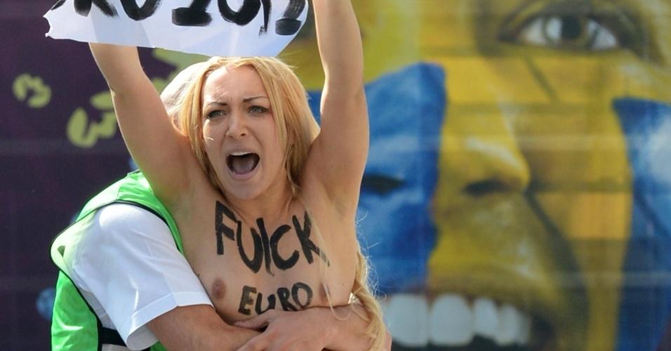 24.jun.2012 - Policial detém manifestante do grupo feminista Femen em protesto no estádio olímpico em Kiev, na Ucrânia, durante partida do campeonato Euro 2012. O grupo tem organizado vários protestos sob o lema