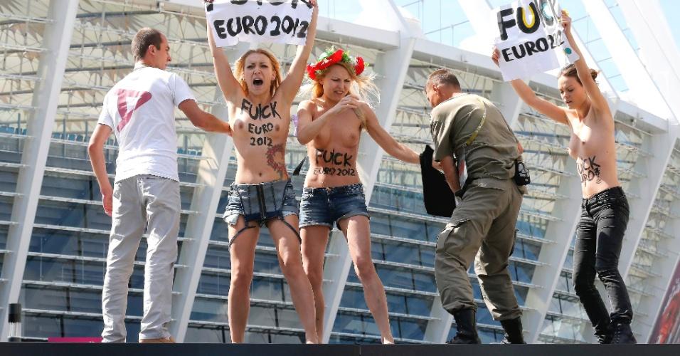 24.jun.2012 - Policial tenta impedir manifestantes do grupo feminista Femen de protestar no estádio olímpico em Kiev, na Ucrânia, durante partida do campeonato Euro 2012. O grupo tem organizado vários protestos sob o lema