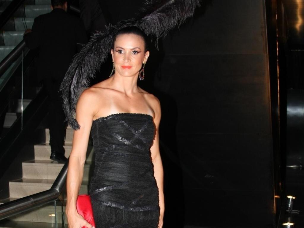 Discreta nas roupas, Maurren deixa para ousar nos acessórios. Aqui, aproveitando a época de carnaval, foi a um baile de gala em São Paulo usando um adereço de plumas na cabeça e uma bolsa vermelha (05/02/2010)