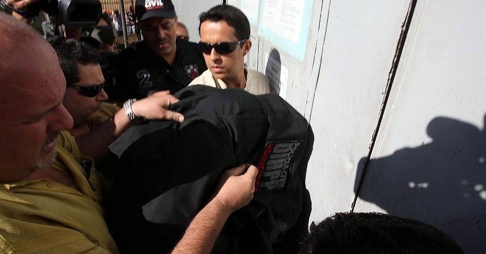 8.jul.2010 - Menor envolvido no caso (sob casaco preto) é transportado pelos policiais na tarde desta quinta-feira (8) no Departamento de Investigações de Belo Horizonte
