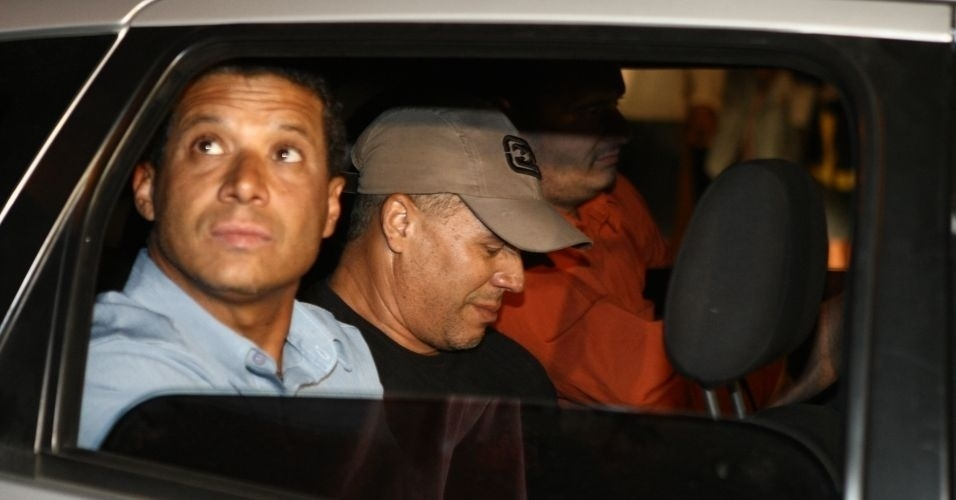 """8.jul.2010 - O ex-policial Marcos Aparecido dos Santos (de boné), conhecido também como """"Bola"""" ou """"Paulista"""", chega ao Departamento de Investigação da Polícia Civil de Belo Horizonte. A polícia acredita que ele tenha executado a morte de Eliza Samudio, ex-namorada do goleiro Bruno"""