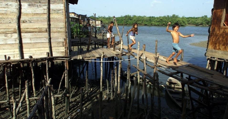 28.jun.2012 - Crianças caminham entre barracos da favela Fé em Deus, que fica sobre mangue em São Luís (MA); o Maranhão, que tem o segundo pior IDH (Índice de Desenvolvimento Humano) do país, atrás somente de Alagoas, registrou maior crescimento populacional da região Nordeste na última década: 16,51%