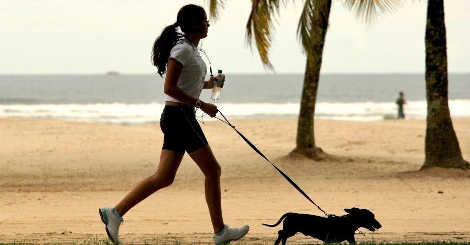 28.jun.2012 - Mulher caminha com cachorro em calçadão de praia de Santos, onde para cada grupo de 100 mulheres há 84 homens, o maior desequilíbrio entre a população dos dois sexos no país