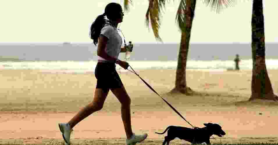 28.jun.2012 - Mulher caminha com cachorro em calçadão de praia de Santos, onde para cada grupo de 100 mulheres há 84 homens, o maior desequilíbrio entre a população dos dois sexos no país - Ricardo Nogueira/Folhapress