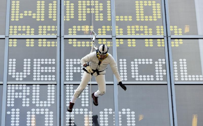 """28.jun.2012 - Suspenso por um cabo a 100 metros de altura, o belga Marc Sluszny faz uma """"corrida vertical"""", em tentativa de entrar para o Livro dos recordes, na torre Belgacom, em Bruxelas, Bélgica"""