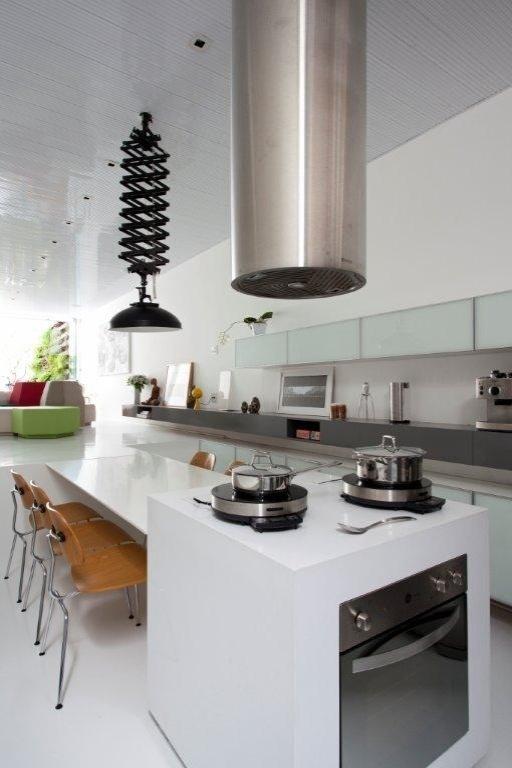 Na cozinha, a mesa de refeições dá continuidade ao piso da sala de estar. Os armários brancos com vidros leitosos desenhados pela arquiteta acomodam eletrodomésticos e utensílios.  A coifa é da Tubo Ar e a luminária tipo pendente pantográfico da Fama Artigos Fotográficos. O projeto é assinado pelos arquitetos e proprietários Lourenço Gimenes (escritório FGMF) e Clara Reynaldo (escritório CR2)