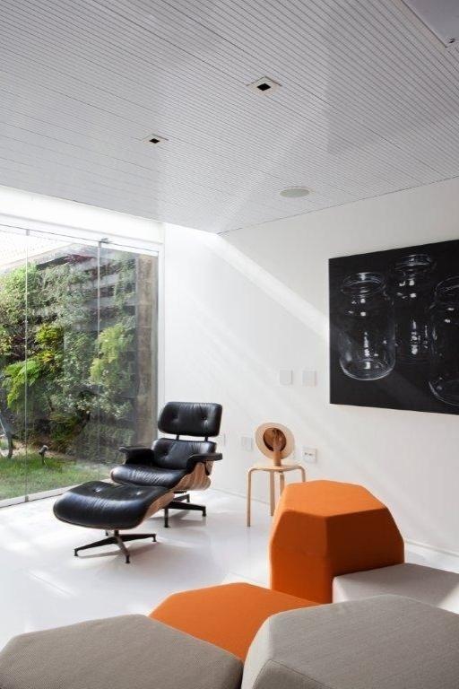 No espaço contíguo à cozinha fica a sala de estar que por sua vez é integrada ao jardim. O charme fica por conta dos pufes da Ovo, em variados formatos, cores e alturas. Tudo junto à incontestável chaise de Charles Eames. O projeto é assinado pelos arquitetos e proprietários Lourenço Gimenes (escritório FGMF) e Clara Reynaldo (escritório CR2)