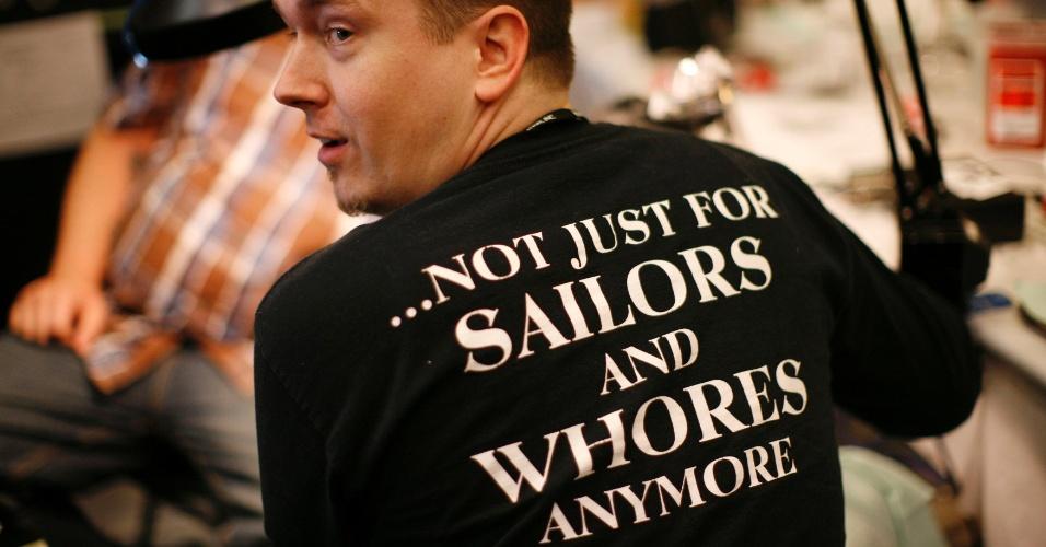 """14.abr.2012 - Homem mostra sua camiseta em defesa das tatuagens, na qual lê-se, em inglês, """"Não é mais apenas para marinheiros e prostitutas"""", num festival de tatuagem em Ohio (EUA)"""