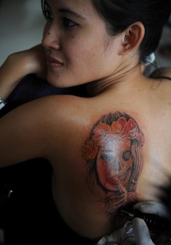23.jun.2012 - Tatuador desenha nas costas de uma mulher durante competição de tatuagem na ilha de Bali, na Indonésia