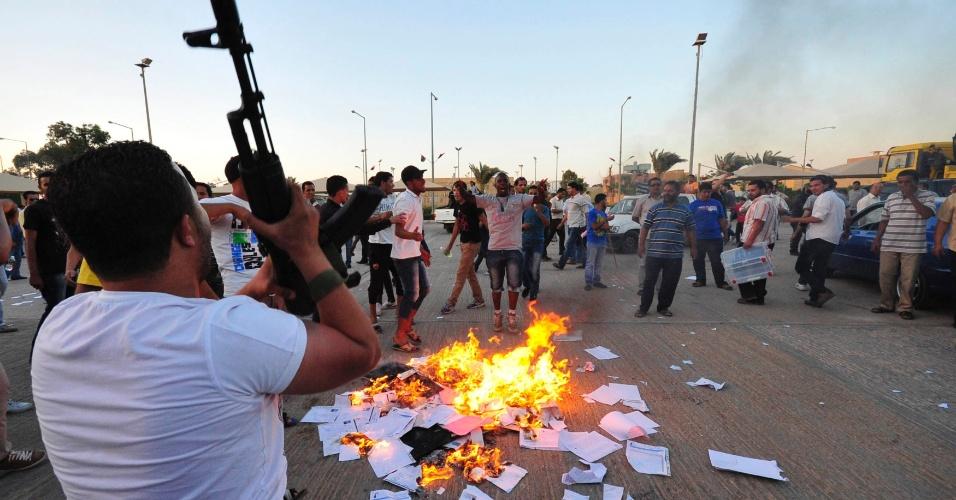 1.jul.2012 - Manifestantes colocam fogo em pilha de materiais de votação depois de invadir o escritório da comissão nacional eleitoral em Benghazi, Líbia. Armados, eles pediam maior autonomia para o país e destruíram computadores e urnas