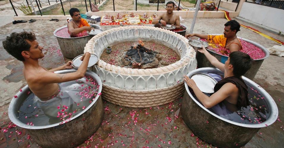 1º.jul.2012 - Sacerdotes indianos sentam-se em caldeirões de água e fazem oferendas durante uma oração especial para a chuva, em Ahmedabad (Índia) neste domingo (1º); os hindus acreditam que as preces acalmam o deus Varuna