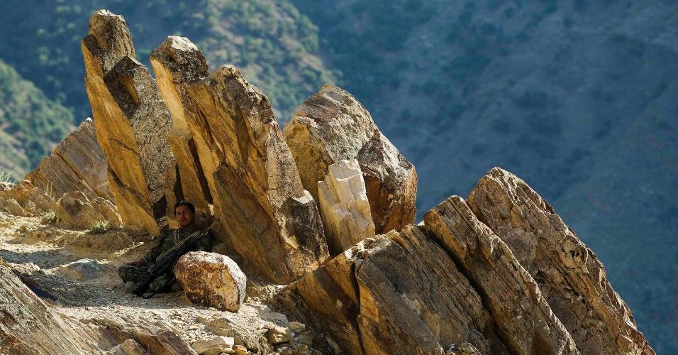 1º.jul.2012 - Um soldado do Exército Nacional Afegão procura sombra debaixo de uma pedra perto do posto de combate Nangalam com vista para o vale do rio Pech na provícia de Kunar (Afeganistão)