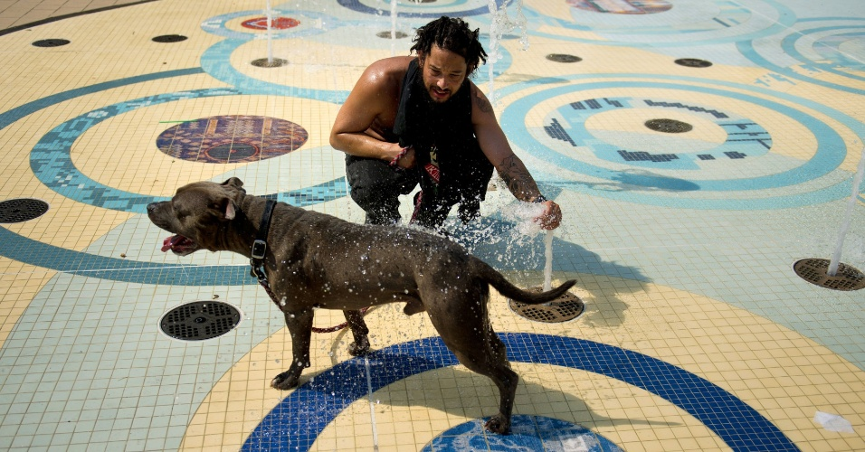 1.jun.2012 - Homem joga água em cachorro em uma fonte em Columbia Heights, Washington, onde a temperatura chega a 40ºC neste verão