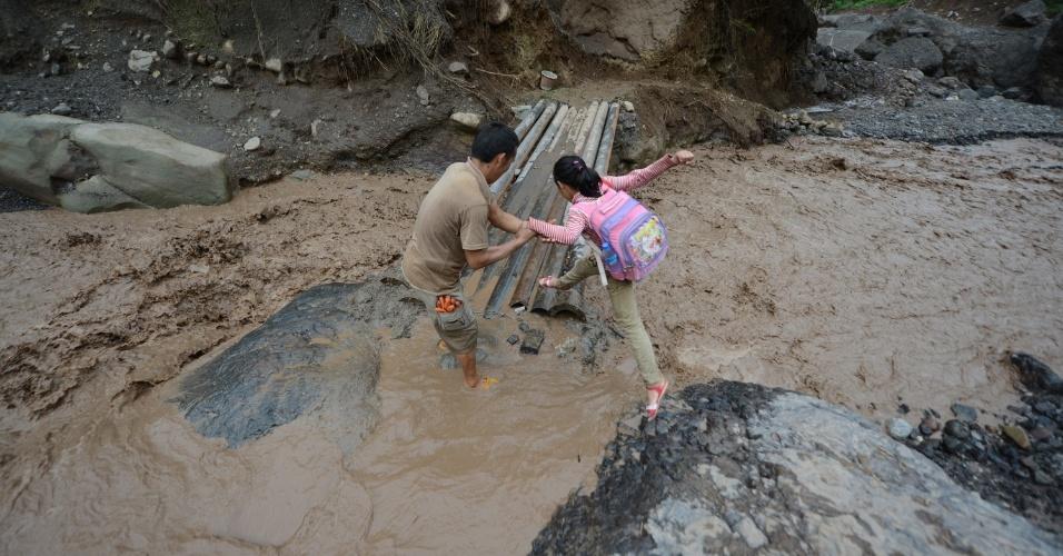 1º.jun.2012 - Menina tenta atravessar uma ponte improvisada para chegar à escola depois de um deslizamento de terra que ocorreu em Ningnan (China) após chuvas torrenciais que atingem a região