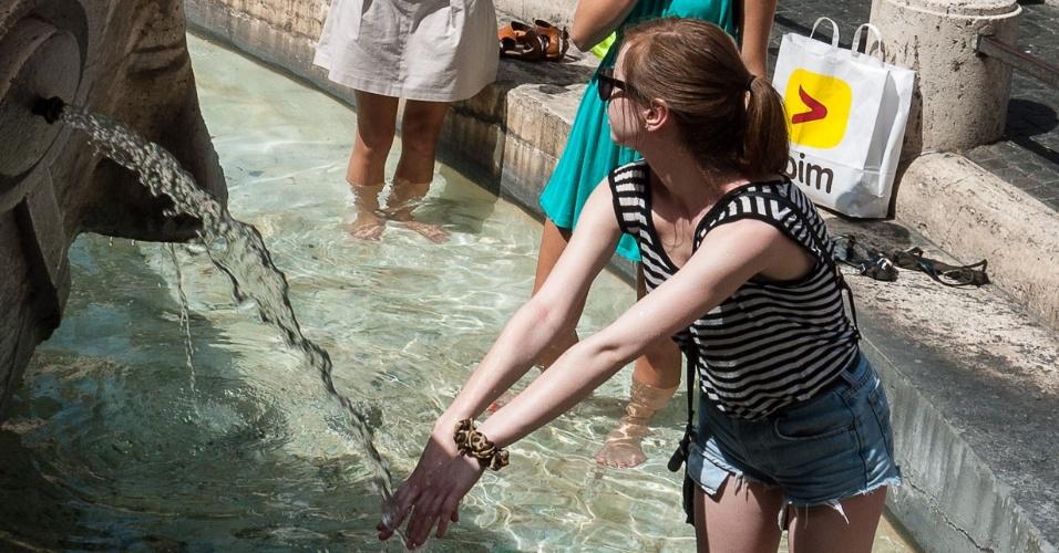 30.jun.3012 - Turistas se refrescam em fonte na Piazza di Spagna, centro de Roma, onde a temperatura está próxima dos 40ºC neste verão
