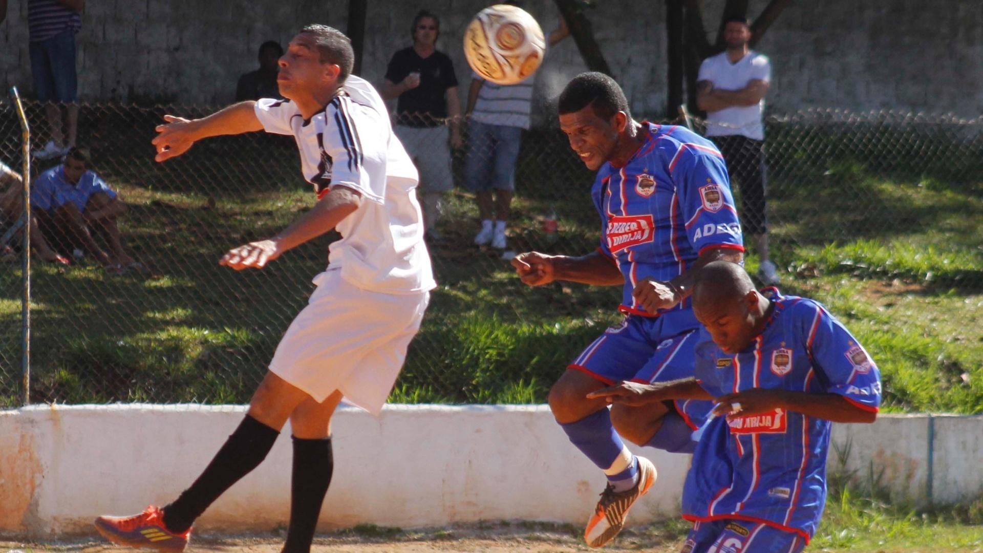 Jogadores disputam lance aéreo em Santos (branco) 0 x 1 Adega (azul)