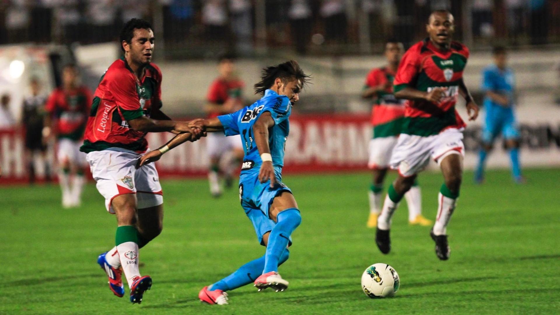 Mesmo sendo puxado, Neymar consegue passar a bola para Borges, no jogo contra a Portuguesa