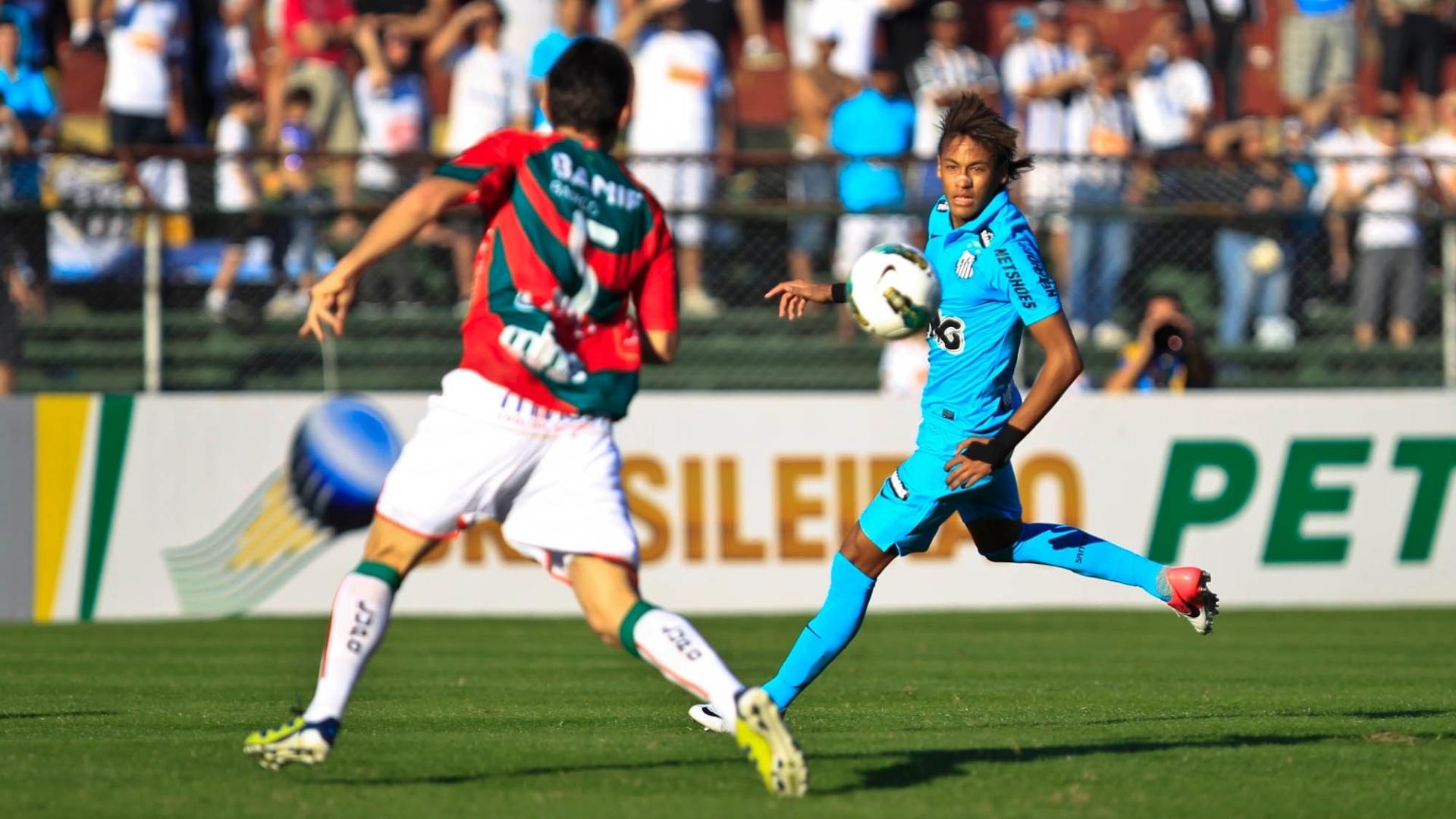 Neymar tenta domínio da bola observado por Lima, zagueiro da Portuguesa, em jogo no Canindé