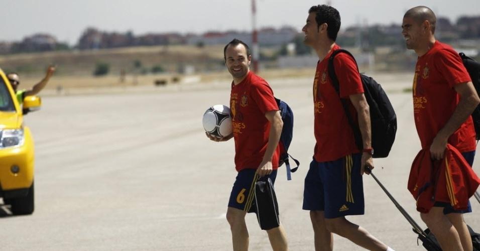 Andres Iniesta, com a bola, caminha ao lado de Sérgio Busquets e Victor Valdés na chegada da delegação espanhola a Madri