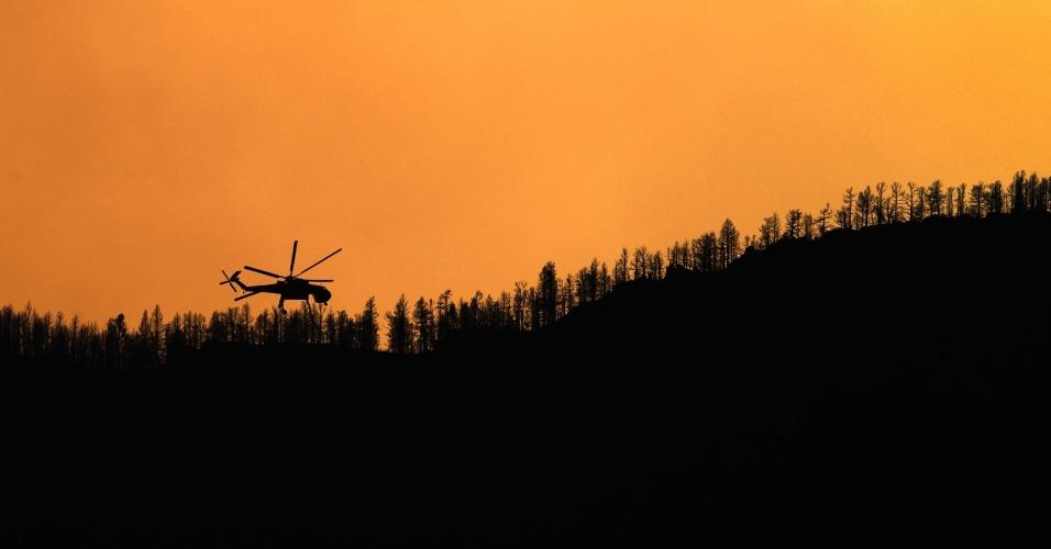 Helicóptero sobrevoa montanha após lançar água para combater incêndio no Cânion Waldo, em Colorado Springs (EUA)