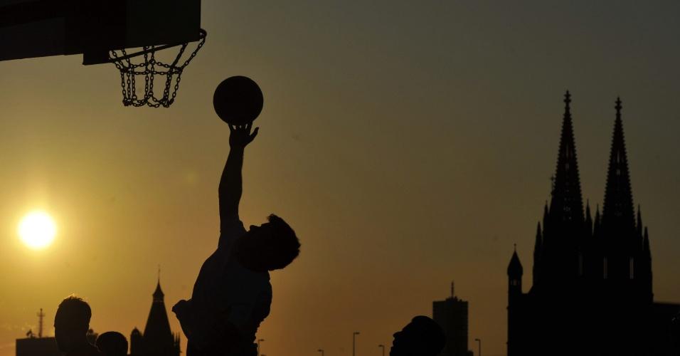 Homem joga basquete, com a Catedral de Colônia (Alemanha) ao fundo, no entardecer desta segunda-feira (2)