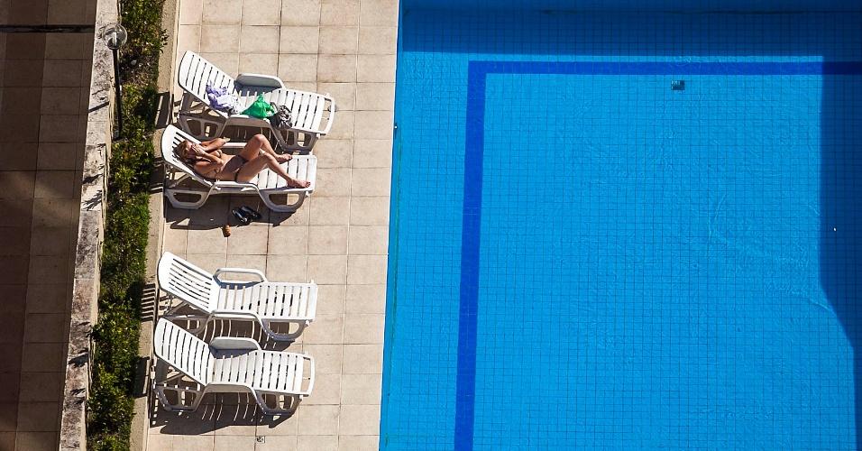 Mulher toma sol na piscina de um prédio localizado na rua Santo Antônio, área central de São Paulo; o tempo seco e quente na capital paulista fez com que a cidade ficasse debaixo de uma faixa de poluição nesta segunda-feira (2)