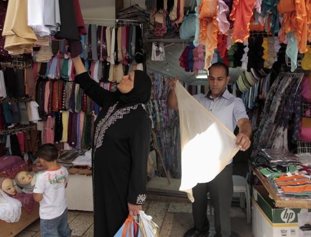 Palestino Maher Abu Rmeileh dobra cachecol na loja de roupas do pai, no lado árabe de Jerusalém