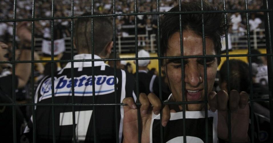 Torcedor do Corinthians demonstra sua fé colado na grade no Pacaembu antes do início da final da Libertadores