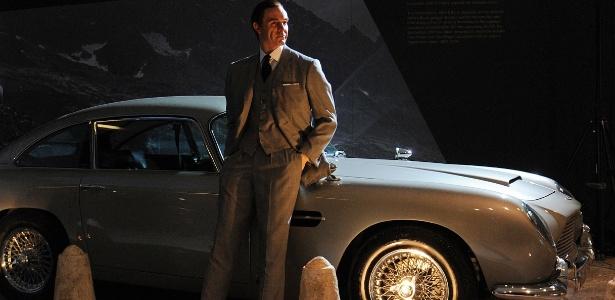 """James Bond em frente ao Aston Martin DB5 usado em """"007 contra GoldenEye"""" (1995). A exposição em homenagem ao meio século de vida da franquia 007 foi montada com a ajuda de produtores dos filmes - AP"""