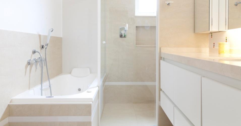 O banheiro da suíte do casal é moderno e prático, com mobiliário criado para deixar tudo à mão. A banheira da Albacete completa o espaço e possibilita momentos de relax aos moradores. O projeto de reforma transformou a casa térrea em sobrado, preservando as características originais