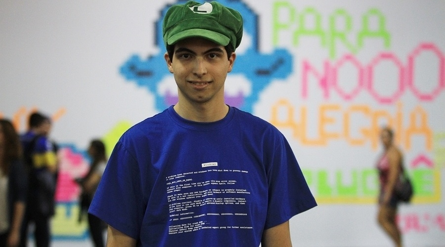 """Por ser um evento de cultura digital, vários participantes do YouPix utilizam camisetas com temática geek. Hugo Demiglio, 21, por exemplo, estava com uma camiseta azul que mostrava o famoso erro da """"tela azul da morte"""" do Windows 98"""