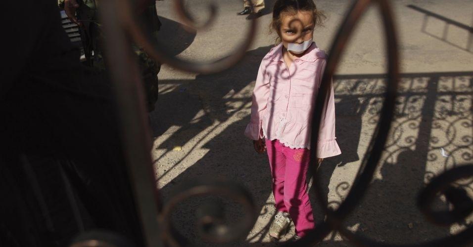 26.nov.2011 - Menina líbia com a boca tapada participa de uma marcha silenciosa, em Tripoli, em apoio às mulheres que foram estupradas durante os recentes combates na Líbia