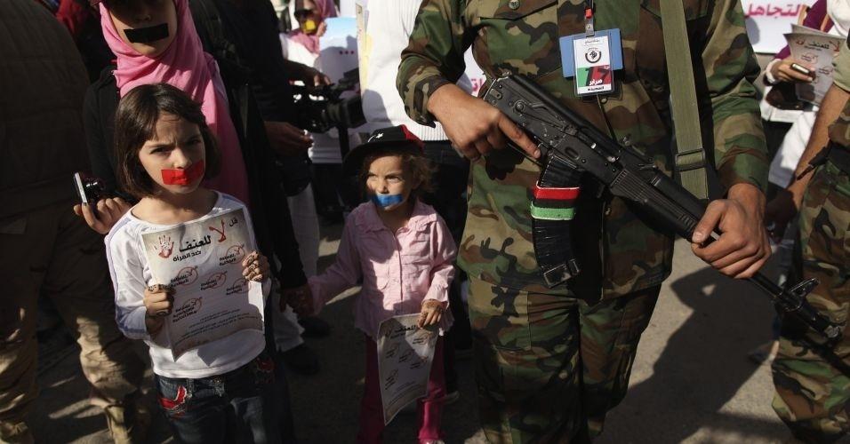 26.nov.2011 - Meninas líbias com as bocas tapadas ao lado de combatente armado; eles participam de uma marcha silenciosa, em Tripoli, em apoio às mulheres que foram estupradas durante os recentes combates na Líbia