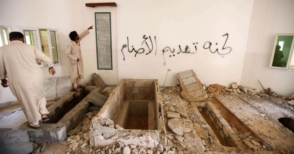 29.out.2011 - Integrantes da tribo do ex-ditador Muammar Gaddafi observam os túmulos violados da mãe, do tio e de outros dois parentes de Gaddafi, em Wadi Jaref, perto de Sirte. Segundo eles, os túmulos foram vandalizados 15 dias antes da morte do ex-líder líbio