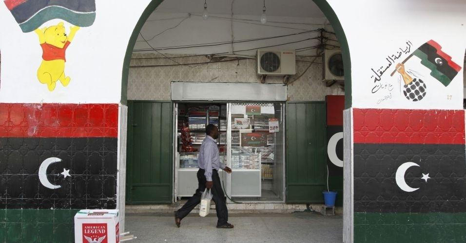 30.out.2011 - Homem caminha em mercado de Trípoli, cuja fachada foi pintada com as cores da nova bandeira da Líbia