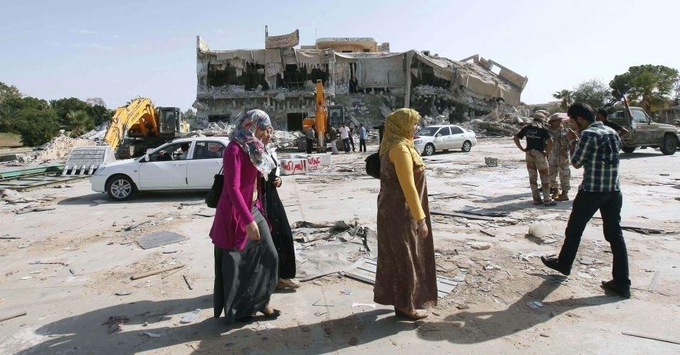 30.out.2011 - Moradores de Trípoli passam em frente à uma das mansões de Gaddafi, que está sendo demolida