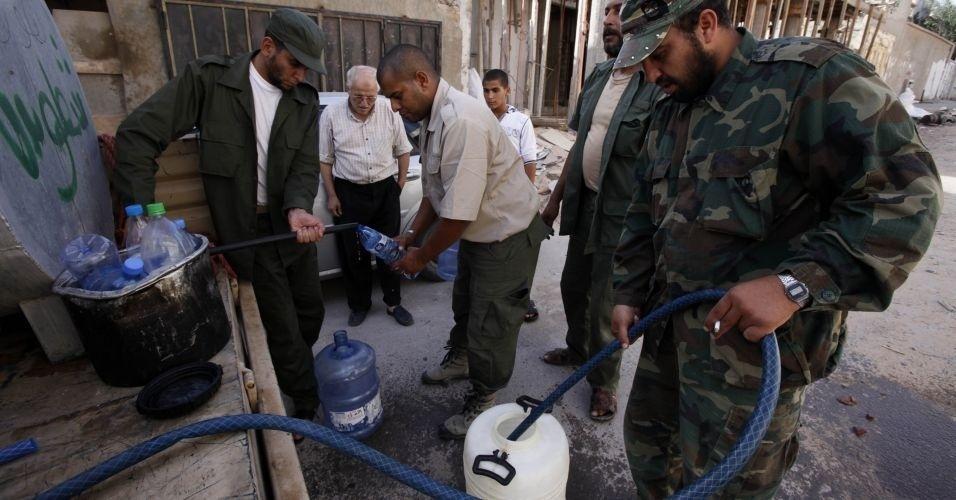 31.out.2011 - Voluntários do Houne village ajudam na distribuição de água em Sirte, cujos moradores que haviam deixado a cidade começam a retornar após a morte de Muammar Gaddafi