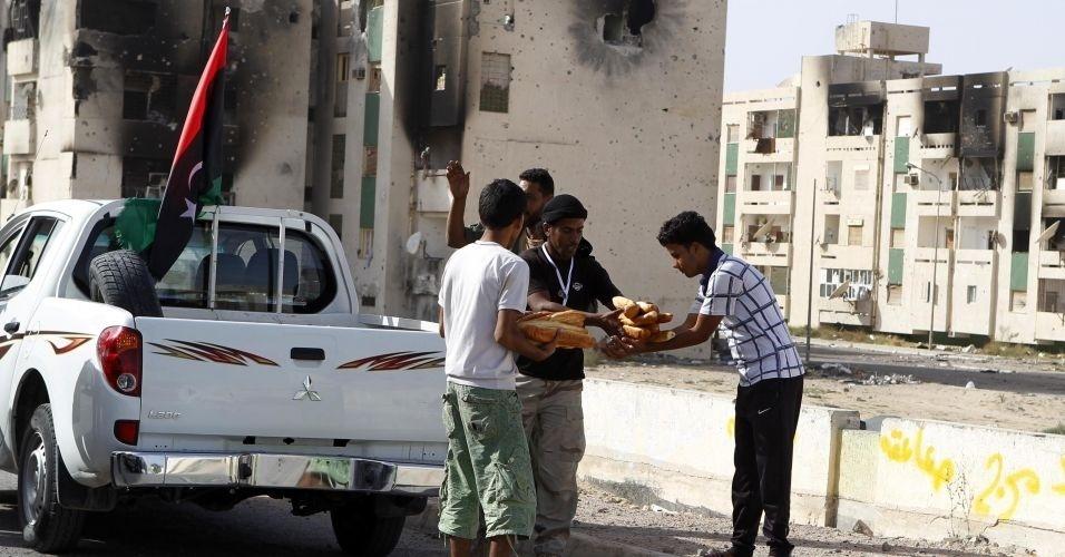 31.out.2011 - Voluntários do Houne village distribuem pão aos moradores de Sirte. Aqueles que haviam deixado a cidade começam a retornar após a morte de Muammar Gaddafi