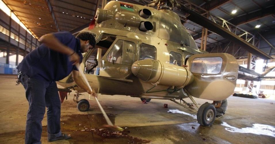 6.jul.2012 - Homem limpa sangue de helicóptero que transportava material de votação para a eleição deste sábado (7) na Líbia quando foi atingido por fogo antiaéreo, próximo à cidade de Benghazi, nesta sexta-feira (6). Uma pessoa que etava a bordo morreu, de acordo com autoridades locais