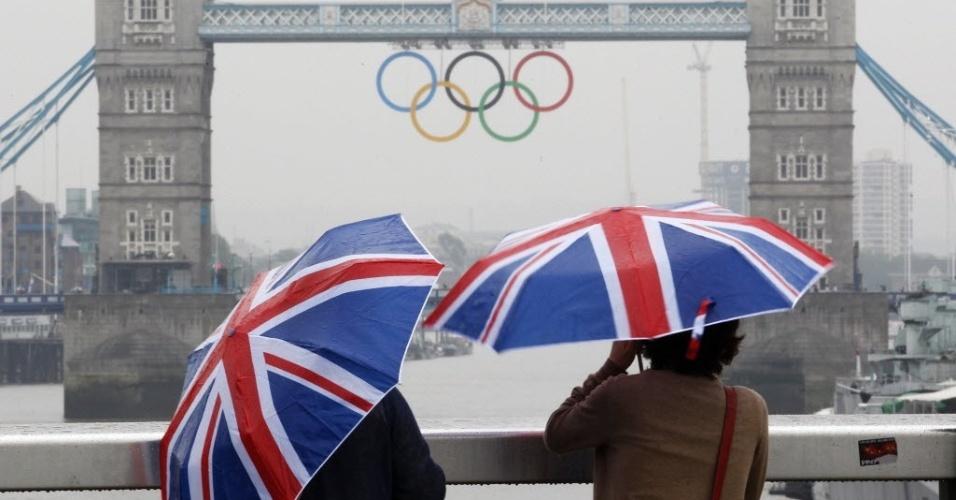 Dois turistas com guarda-chuvas estampados coma bandeira do Reino Unido fazem fotos da Tower Bridge, decorada com os anéis olímpicos