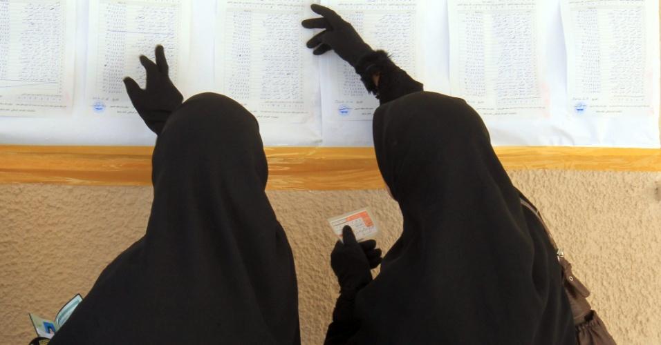 7.jul.2012 - Duas mulheres líbias buscam seus nomes para votar nas eleições legislativas no país em um colégio eleitoral na cidade de Bengasi. Esta é a primeira eleição após quase 50 anos de domínio de Muammar Gaddafi