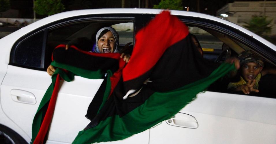 7.jul.2012 - Família tremula bandeira do país para celebrar o fim das votações legislativas na cidade de Sirte, na Líbia