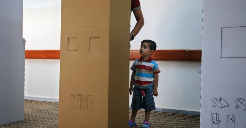 7.jul.2012 - Garoto líbio observa pai na cabine de votação durante as eleições legislativas na cidade de Misrata. Vários eleitores fizeram fila para votar na primeira eleição nacional após décadas de ditadura de Muammar Gaddafi